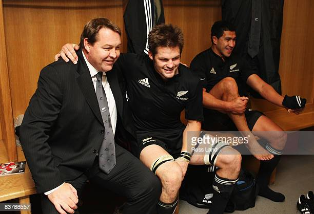 Steve Hansen forwards coach Richie McCaw captain and Mils Muliaina of the All Blacks celebrate in the dressing room with the winners trophy following...