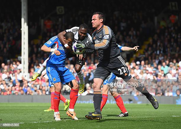 Steve Harper of Hull takes the ball cleanly as Liam Rosenior tangles with Hugo Rodallega of Fulham during the Barclays Premier League match between...