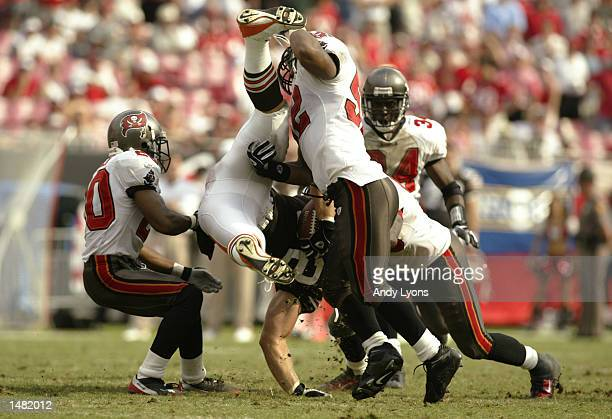 Steve Heiden of the Cleveland Browns is tackled by Tampa Bay Buccaneers players during the game on October 13 2002 at Raymond James Stadium in Tampa...