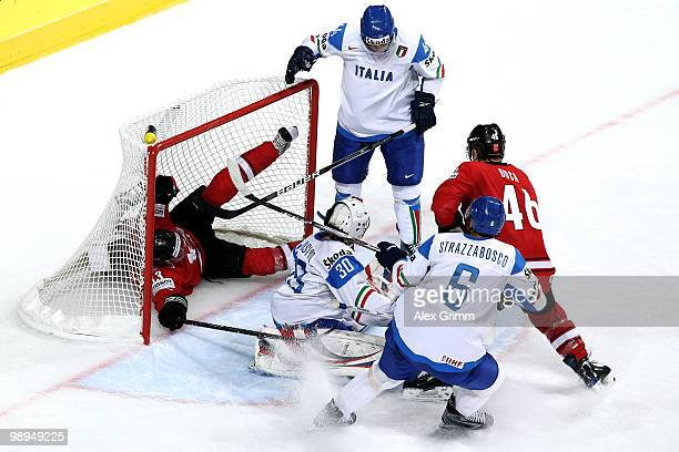 Steve Hirschi of Switzerland falls into the goal as he is challenged by Nicholas Plastino and goalkeeper Daniel Bellissimo of Italy during the IIHF...