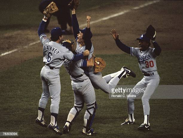 Steve Howe of the Los Angeles Dodgers jumps into the arms of catcher Steve Yeager of the Los Angeles Dodgers with Steve Garvey and Derrel Thomas also...