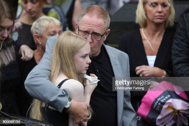 Steve Howe the husband of Manchester attack victim Alison Howe embraces family members as Alison's funeral cortege leaves St Anne's Church on June 23...