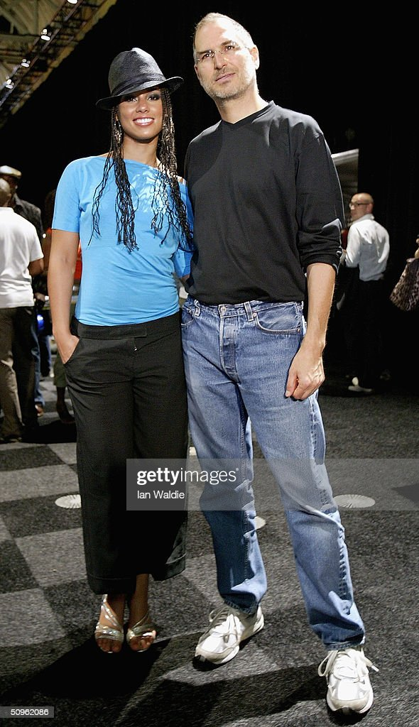 Steve Jobs, Chief Executive Officer of Apple computers poses for a photo with R&B singer Alicia Keys as he launches iTunes Music Store in the territories of Great Britain, Germany and France, on June 15, 2004 in London. The iTunes store allows users to buy and download albums or individual songs from a library of 700,000 songs.