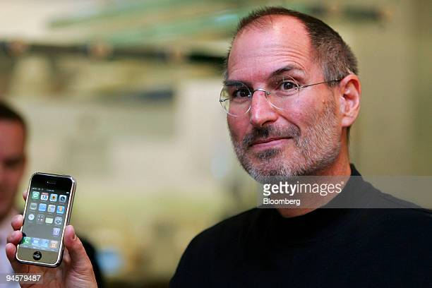 Steve Jobs, chief executive officer of Apple Corp., holds an iPhone at the Apple store in Regent Street, London, U.K., on Tuesday, Sept. 18, 2007....