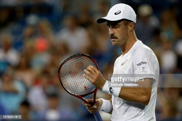 Steve Johnson adjusts his racquet between points while playing Novak Djokovic of Serbia during the Western Southern Open at Lindner Family Tennis...