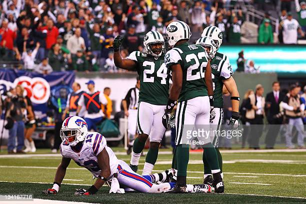 Steve Johnson of the Buffalo Bills lies on the ground as Darrelle Revis, Brodney Pool, and Jim Leonhard of the New York Jets celebrate a broken up...