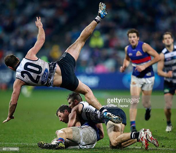 Steve Johnson of the Cats jumps over Dale Morris of the Bulldogs and Shane Kersten of the Cats during the round 16 AFL match between the Geelong Cats...