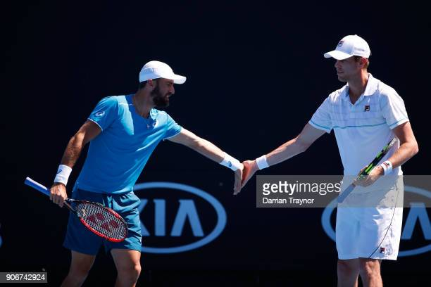 Steve Johnson of the United States and Sam Querrey of the United States talk tactics in their second round men's doubles match against Pablo Andujar...