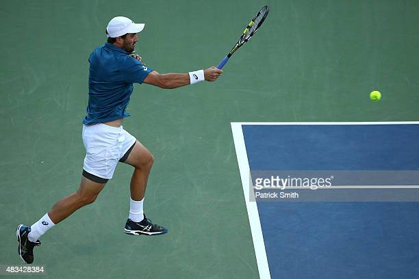 Steve Johnson of the United States returns a shot to John Isner of the United States during the Citi Open at Rock Creek Park Tennis Center on August...