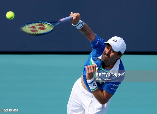 Steve Johnson of the United States serves during his men's singles first round match against Yannick Hanfmann of Germany on Day 3 of the 2021 Miami...