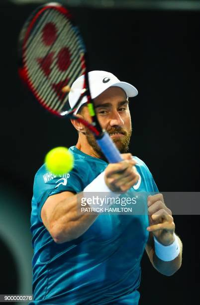 Steve Johnson of the US hits a return against Alex De Minaur of Australia during their first round match at the Brisbane International tennis...