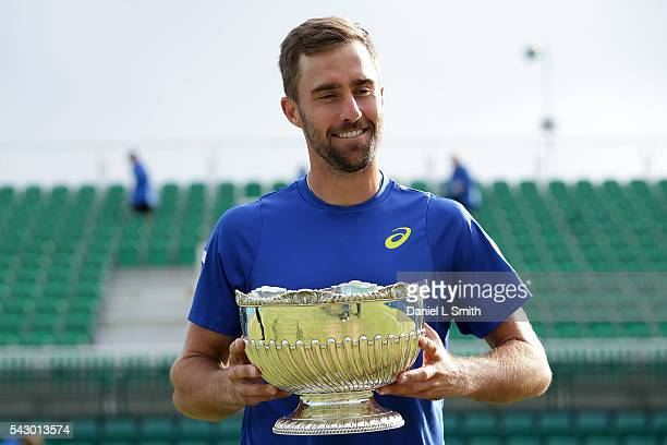 Steve Johnson of USA walks off Centre Court with his trophy after winning the men's singles match against Pablo Cuevas of Uruguay during day six of...