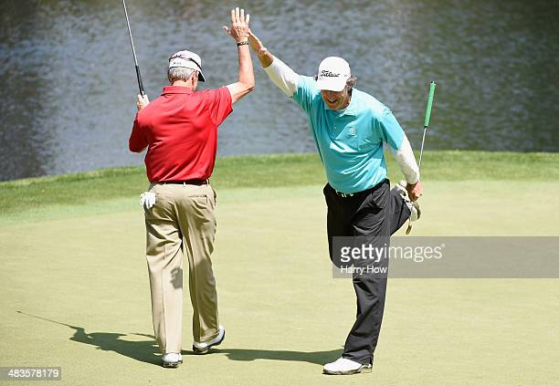 Steve Jones celebrates with Larry Mize after holing a putt on the ninth green during the 2014 Par 3 Contest prior to the start of the 2014 Masters...