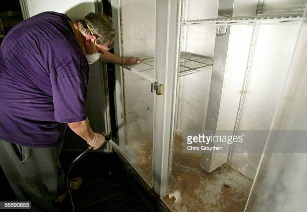Steve Latter owner of Tujaques restaurant in the French Quarter washes out a refrigerator that held spoiled and rotting food during cleanup after...