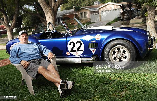 Steve Legino poses with a Cobra 427 which he help rebuild on the lawn in front of his home in Glendale California October 20 2011 Legino grew up in...