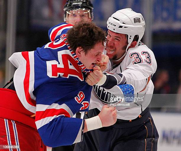 Steve MacIntyre of the Edmonton Oilers fights with Derek Boogaard during the third period of a hockey game at Madison Square Garden on November 14...