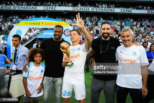 Steve Mandanda Florian Thauvin and Adil Rami of Marseille present the world Cup trophy to the crowds during the French Ligue 1 match between...