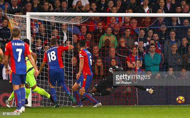 Steve Mandanda of Crystal Palace dives in vain as Emre Can of Liverpool scores his team's first goal during the Premier League match between Crystal...