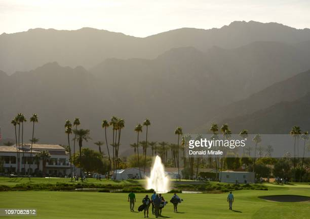 Steve Marino of the United States, Tyrone Van Aswegen of South Africa, and their caddies walk down the fairway during the second round of the Desert...