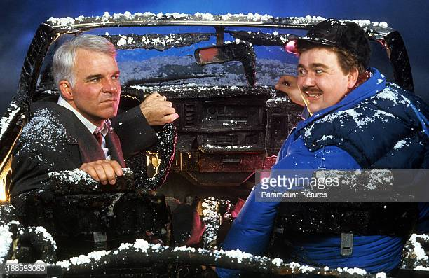 Steve Martin and John Candy sit in a destroyed car in a scene from the film 'Planes Trains Automobiles' 1987