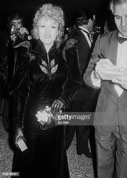 Steve Martin sigining autographs Bernedette Peters posing for the camera in a velvet coat circa 1980 New York