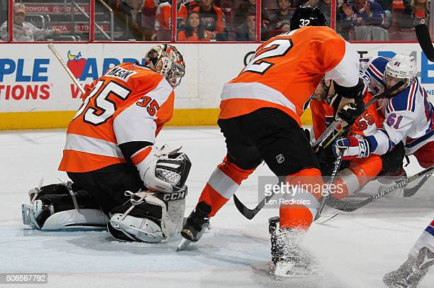 Steve Mason, Mark Streit and Nick Schultz of the Philadelphia Flyers battle to cover the puck against Rick Nash of the New York Rangers on January...