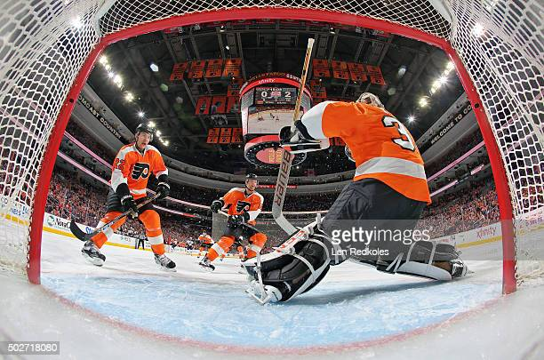 Steve Mason of the Philadelphia Flyers slides across the crease to make the glove save with teammates Luke Schenn and Sean Couturier against the St...