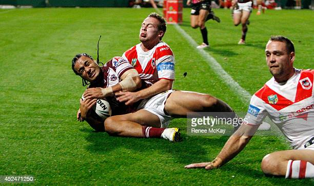Steve Matai of the Sea Eagles scores a try in the tackle of Adam Quinlan of the Dragons during the round 19 NRL match between the St George Dragons...