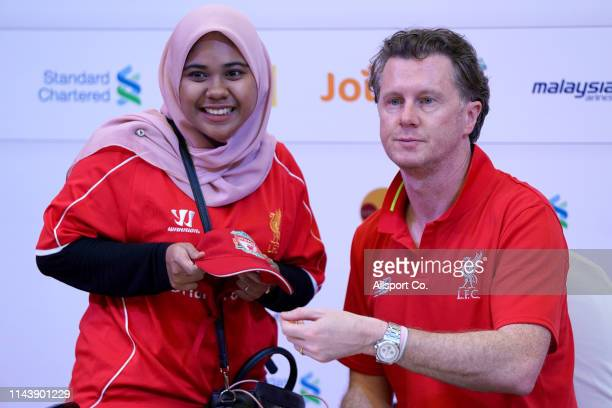 Steve McManaman former Liverpool player and legend poses with a fan after signing an autograph during the meet and greet fans session at the One...