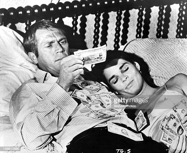 Steve McQueen and Ali MacGraw counting their money in bed in a scene from the film 'The Getaway' 1972