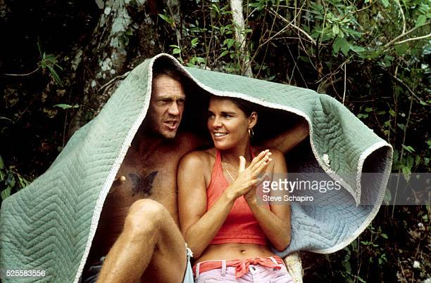Steve McQueen and girlfriend Ali MacGraw take cover under blanket as it rains on the set of Papillon on location in Jamaica