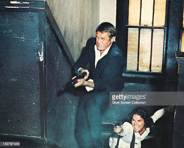 Steve McQueen US actor and Ali MacGraw US actress in a shootout in a publicity still issued for the film 'The Getaway' USA 1972 The crime drama...