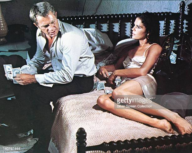 Steve McQueen , US actor, and Ali MacGraw, US actress, sitting on a bed counting banknotes in a publicity still issued for the film, 'The Getaway',...