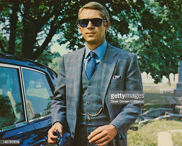 Steve McQueen US actor wearing sunglasses with a grey suit a blue shirt and dark blue tie in a publicity image issued for the film 'The Thomas Crown...