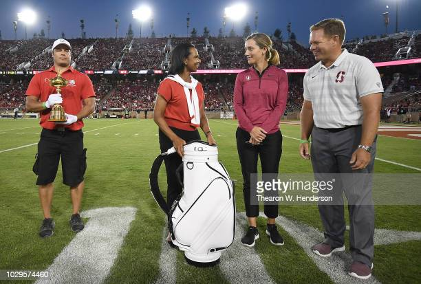 Steve Meinke with the Ryder Cup Trophy with Condoleezza Rice presenting a golf bag to Anne Walker and Conrad Ray on the field during a time out of...