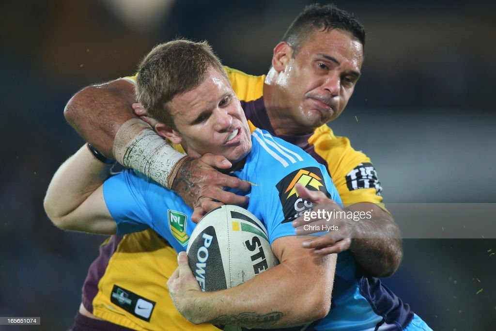 Steve Michaels of the Titans is tackled by Justin Hodges of the Broncos during the round five NRL match between the Gold Coast Titans and the Brisbane Broncos at Skilled Park on April 5, 2013 in Gold Coast, Australia.