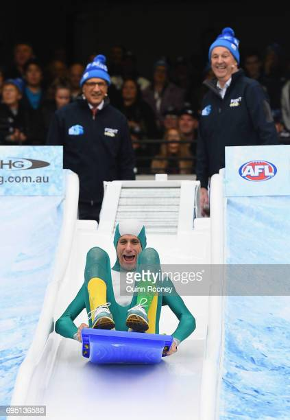 Steve Moneghetti goes down the Freeze MND slide during the round 12 AFL match between the Melbourne Demons and the Collingwood Magpies at Melbourne...