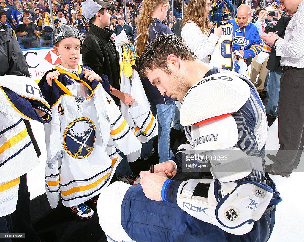 Steve Montador #4 of the Buffalo Sabres signs an autograph for a young fan as he and his teammates give away their game jerseys following their 4-3 win over the Philadelphia Flyers at HSBC Arena on March 8, 2011 in Buffalo, New York.