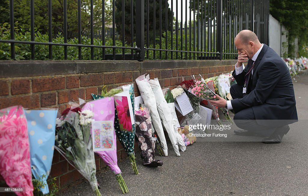Steve Mort, head teacher of Corpus Christi Catholic College, reads the hundreds of tributes left in honour of slain teacher Ann Maguire on April 30, 2014 in Leeds, England. A fifteen year old male student has been arrested in connection with the death of teacher Ann Maguire, 61, who died from multiple stab wounds after the attack in her classroom at Corpus Christi Catholic College.