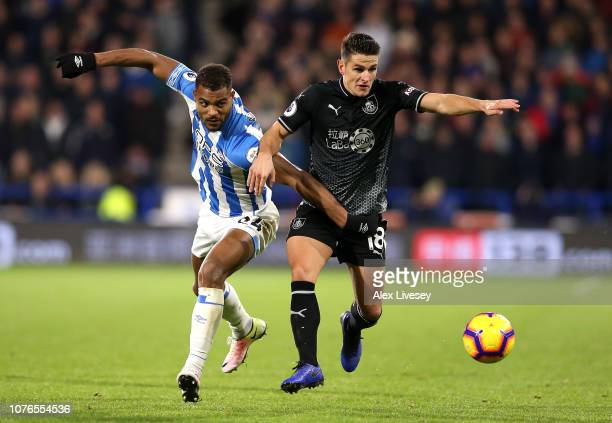 Steve Mounie of Huddersfield Town and Ashley Westwood of Burnley clash during the Premier League match between Huddersfield Town and Burnley FC at...