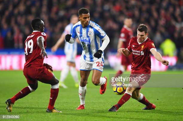 Steve Mounie of Huddersfield Town ateempts to go between James Milner and Sadio Mane of Liverpool during the Premier League match between...