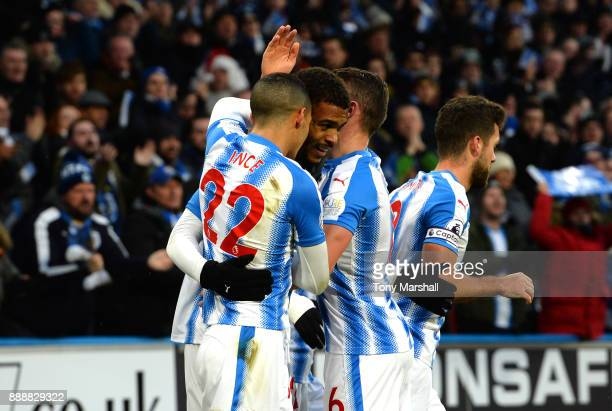 Steve Mounie of Huddersfield Town celebrates after scoring his sides first goal with his team mates during the Premier League match between...