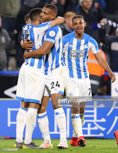 Steve Mounie of Huddersfield Town celebrates after scoring his team's first goal with team mates during the Premier League match between Huddersfield...