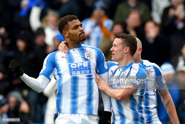 Steve Mounie of Huddersfield Town celebrates with teammate Jonathan Hogg after scoring his sides third goal during the Premier League match between...
