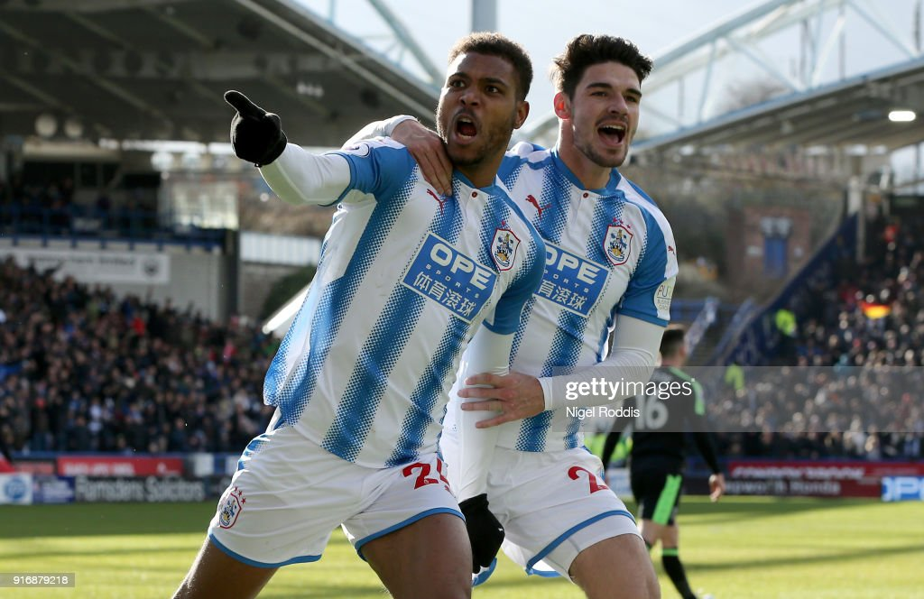 Steve Mounie of Huddersfield Town celebrates with teammate Christopher Schindler after scoring his sides second goal during the Premier League match between Huddersfield Town and AFC Bournemouth at John Smith's Stadium on February 11, 2018 in Huddersfield, England.