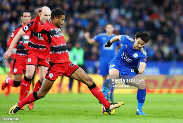 Steve Mounie of Huddersfield Town challenges Shinji Okazaki of Leicester City during the Premier League match between Leicester City and Huddersfield...