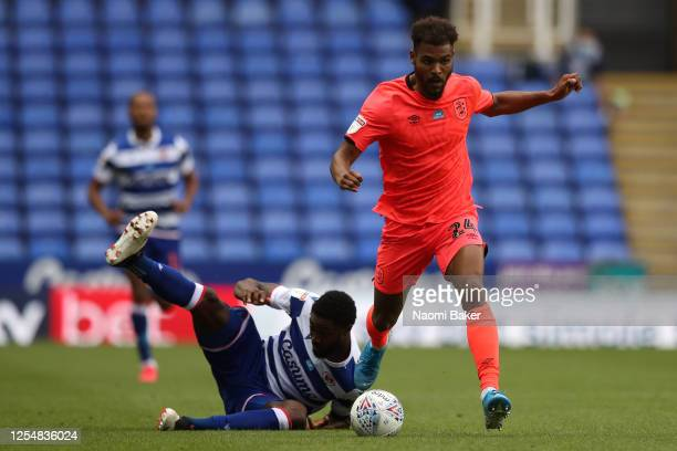 Steve Mounie of Huddersfield Town escapes the challenge of Tyler Blackett of Reading during the Sky Bet Championship match between Reading and...