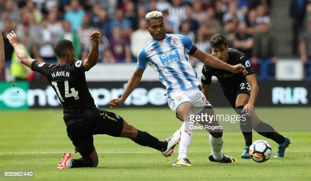 Steve Mounie of Huddersfield Town is challenged by Isaac Hayden and Mikel Merino during the Premier League match between Huddersfield Town and...