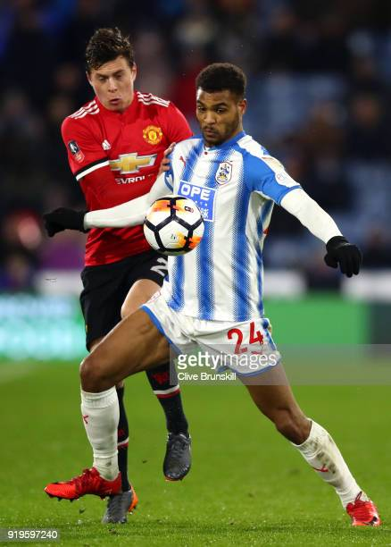 Steve Mounie of Huddersfield Town is challenged by Victor Lindelof of Manchester United during the The Emirates FA Cup Fifth Round between...