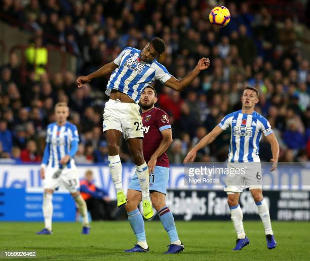 Steve Mounie of Huddersfield Town jumps for the ball under pressure fron Robert Snodgrass of West Ham United during the Premier League match between...